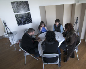 Daylit room: five people sit round a circular table with white tablecloth, which has zips sewn into it in front of each of their places. They look deep in thought
