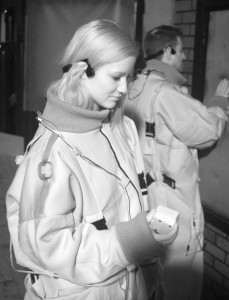 Infrared shot in a pitch dark space. A woman holds a cube device, behind her a man is touching a fabric panel set into a wall. They both wear boilersuits