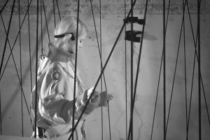 Infrared shot in a pitch black space. A participant walks between rows of vertical ropes, touching them either side with her hands. She wears a boiletsuit and special headphones