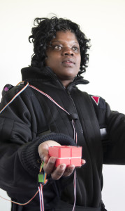 A black woman shown from waist up in her hand she holds a red cube which is attached by long wires to the shoulder of her black full length overalls