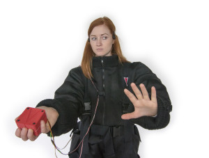 A woman reaches out as if feeling her way, dressed in a black quilted  suit, wearing headphones and holding a red cube device in one hand which is attached to the suit by wires